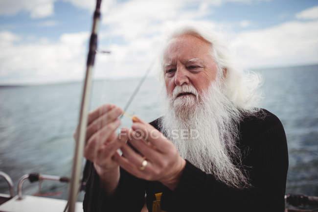 Enfoque selectivo del pescador ajuste gancho de pesca en barco de pesca - foto de stock