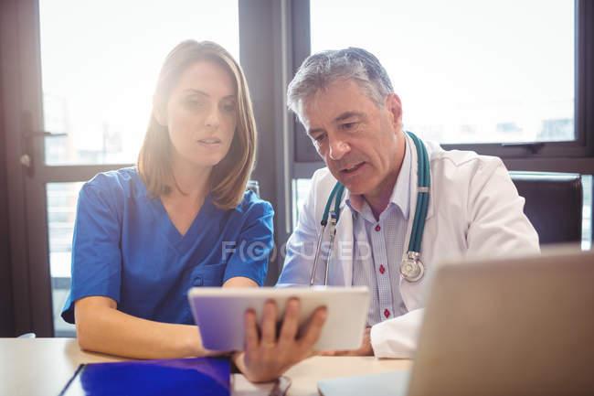 Medico discutendo con l'infermiera su tablet digitale in ospedale — Foto stock