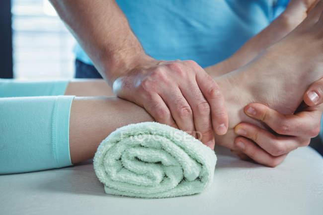 Обітнутого зображення чоловічого фізіотерапевт, даючи масаж ступень пацієнтки в клініці — стокове фото