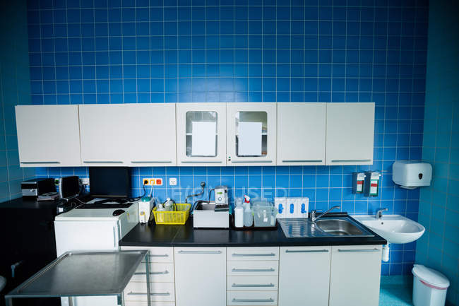 Cabinets, refrigerator, wash basin, worktop and sink in hospital room — Stock Photo