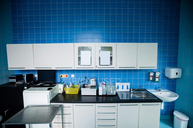 Gabinetes, nevera, lavabo, encimera y lavabo en la habitación del hospital - foto de stock