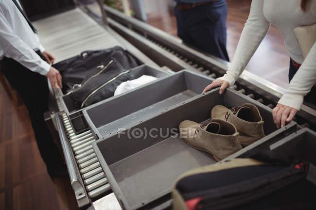 Sapatos de mulher colocando na bandeja para segurança verificar no aeroporto — Fotografia de Stock