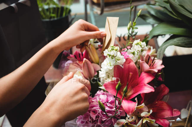 Hands of female florist arranging flower bouquet in the flower shop — Stock Photo