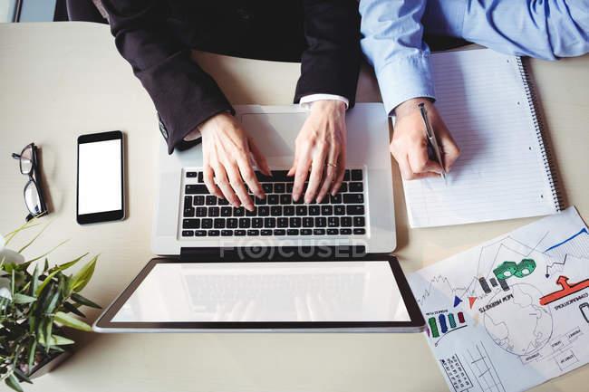 Immagine ritagliata di uomo d'affari e collega seduto a tavola in ufficio — Foto stock