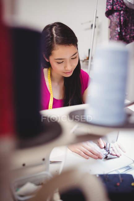 Femme couturière couture sur machine à coudre en studio — Photo de stock