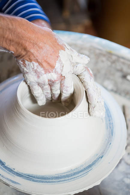 Cropped image of potter making pot in pottery workshop — Stock Photo