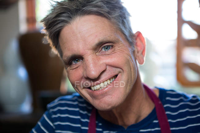 Portrait of happy male potter in pottery workshop — Stock Photo