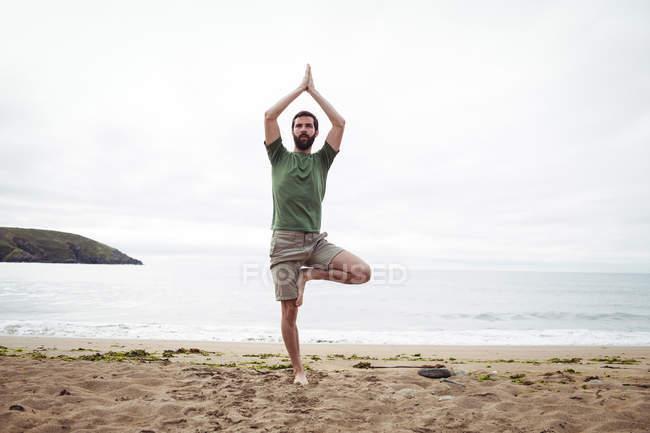 Mann macht Yoga am Strand — Stockfoto