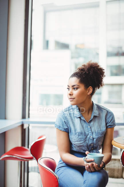 Smart thoughtful woman with coffee cup while sitting at table in restaurant — Stock Photo