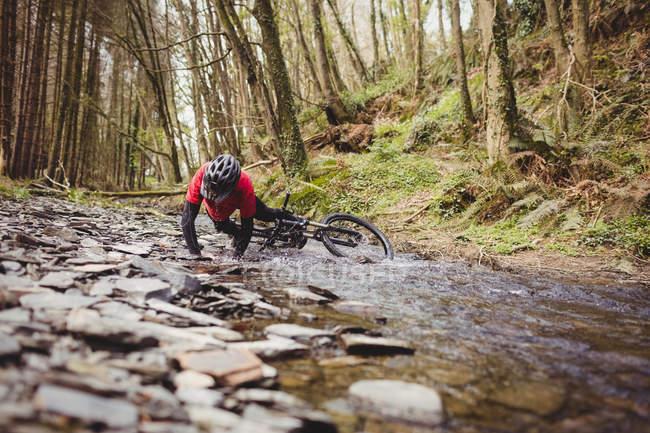Mountain biker caduto nel torrente nella foresta — Foto stock