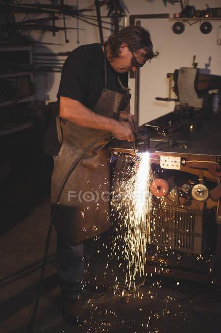 Blacksmith working at work shop — Stock Photo