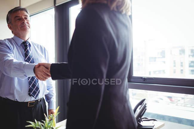 Кадроване зображення бізнес-леді і бізнес-леді потискують один одному руки в офісі — стокове фото