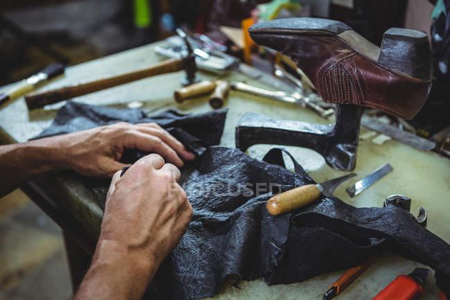 Händen der Schuhmacher schneiden ein Stück Stoff in Werkstatt — Stockfoto