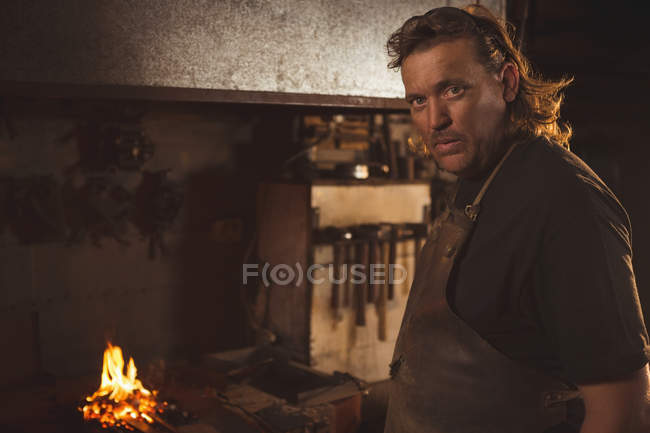 Portrait of blacksmith in protective workwear at work shop — Stock Photo
