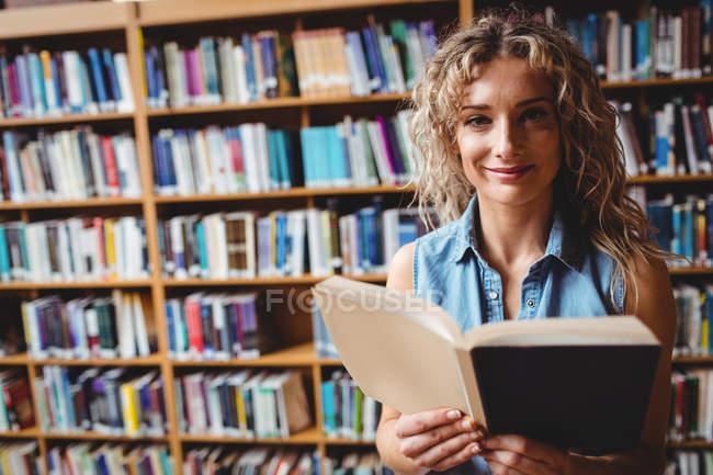 Libro di lettura di bella donna in biblioteca — Foto stock