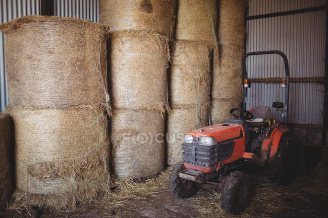 Stack of hay bales and tractor in barn — Stock Photo