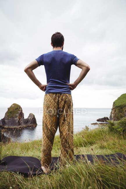 Задній вид на людину, стоячи з руки на стегна на скелі — стокове фото