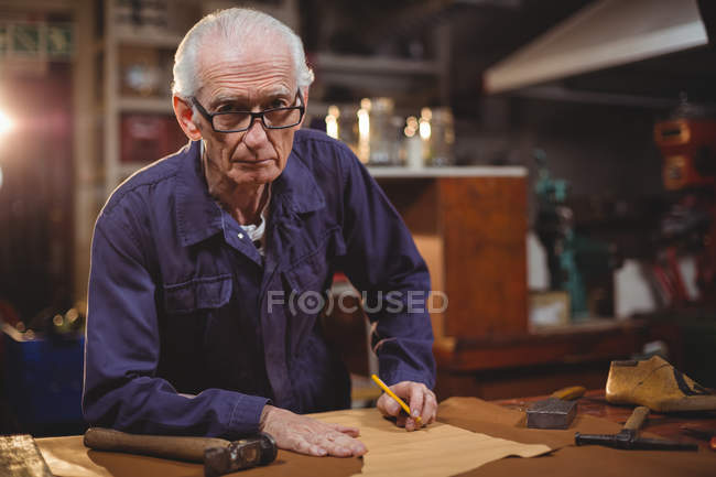 Sapateiro sênior cortando um pedaço de couro na oficina — Fotografia de Stock