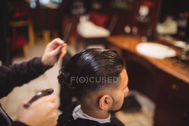 Man getting his hair trimmed in barber shop — Stock Photo