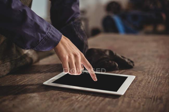 Cropped image of female welder using digital tablet in workshop — Stock Photo