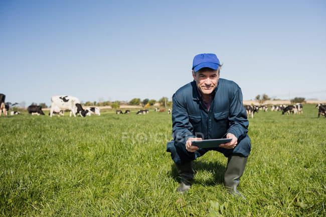 Porträt eines Landarbeiters, der Tablet-Computer benutzt, während er auf einer Wiese hockt — Stockfoto
