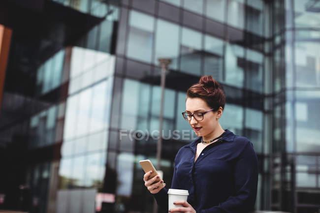 Giovane donna che utilizza il telefono cellulare contro edificio per uffici — Foto stock