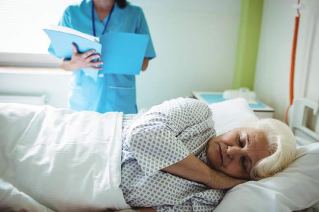 Patiente âgée dormant sur un lit d'hôpital — Photo de stock