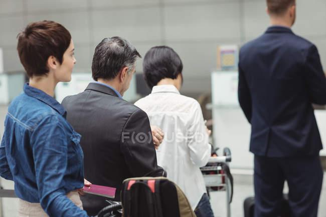 Passagiere warten mit Gepäck in der Warteschlange am Check-in-Schalter im Flughafenterminal — Stockfoto