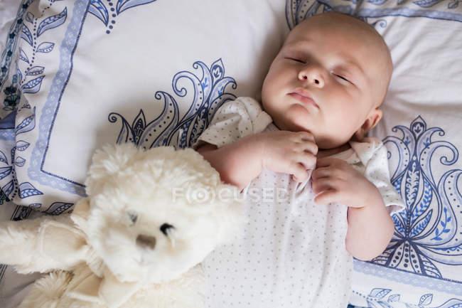 Bebé durmiendo en la cama con oso de peluche en el dormitorio en casa - foto de stock