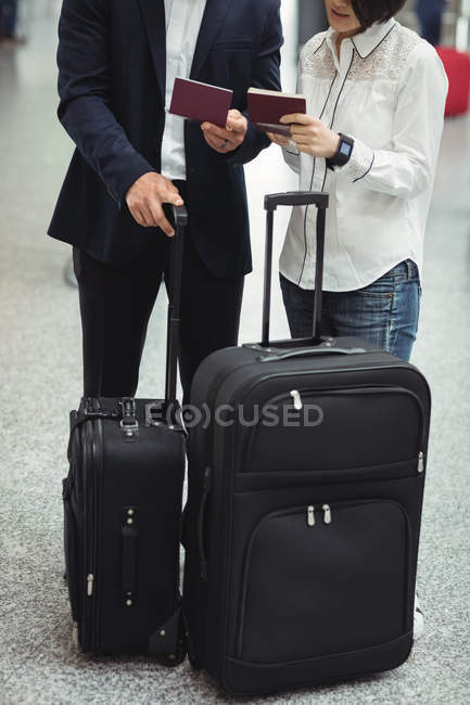 Business man and woman checking their passports in airport terminal — Stock Photo