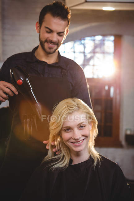 Ritratto di donna sorridente che si fa asciugare i capelli con un asciugacapelli dal parrucchiere — Foto stock