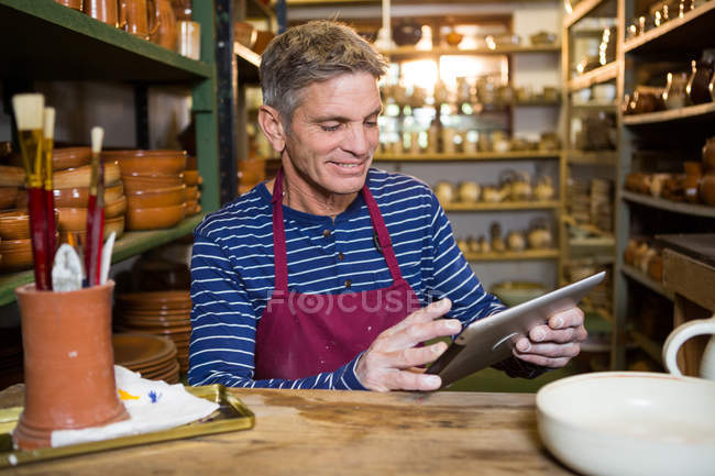 Male potter using digital tablet in pottery workshop — Stock Photo