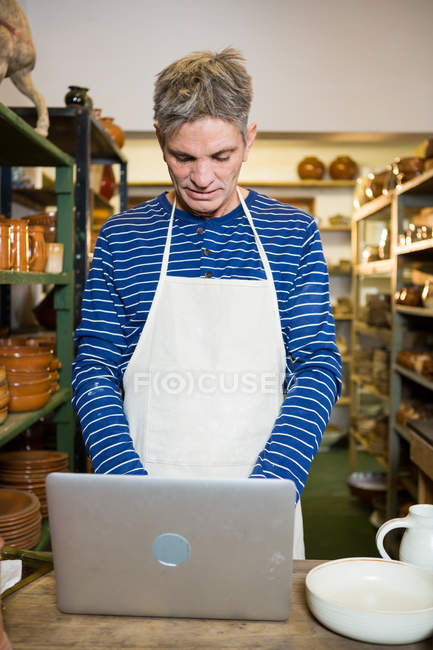Male potter using laptop in pottery workshop — Stock Photo