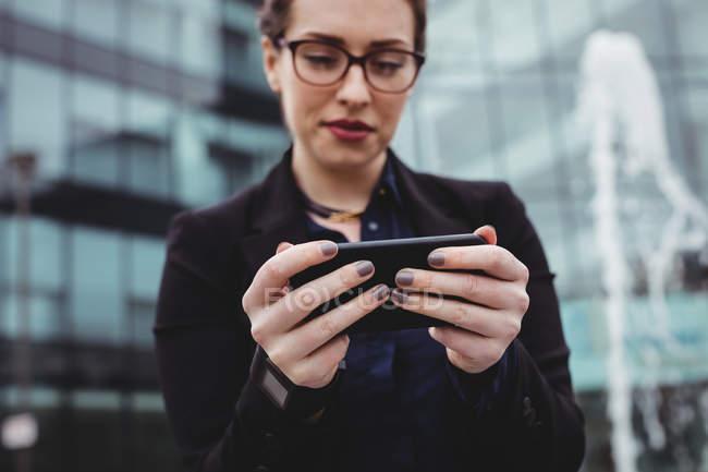 Бизнесвумен, использующая мобильный телефон против офисного здания — стоковое фото