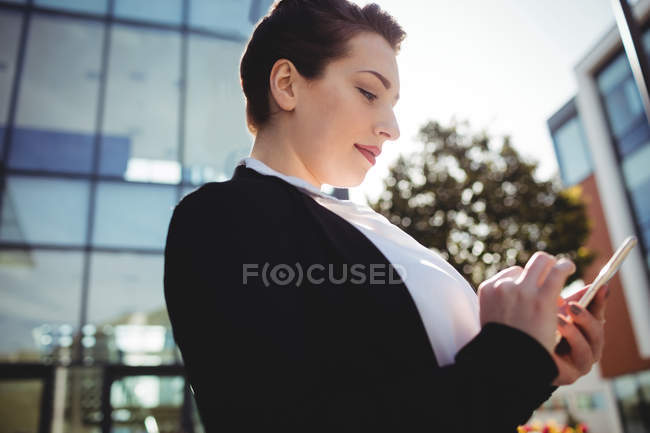 Young woman using mobile phone against building — Stock Photo