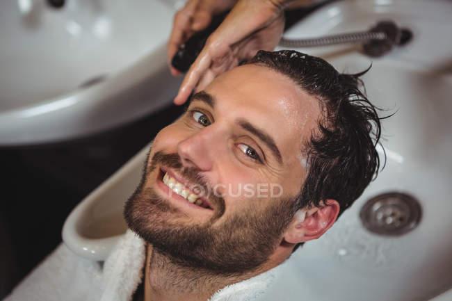 Портрет усміхнений чоловік отримує його мити волосся в салон — стокове фото