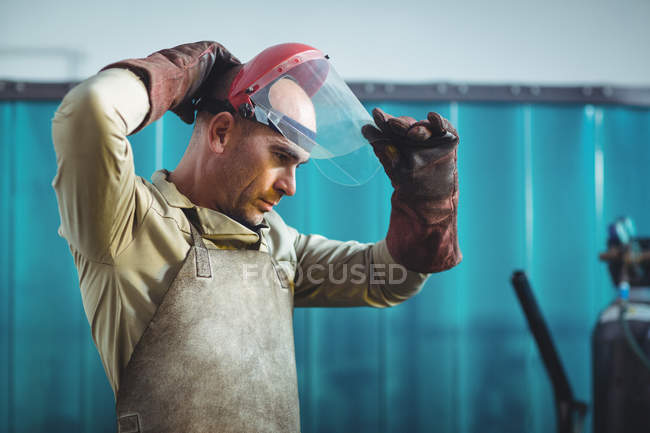 Male welder wearing protective helmet in workshop — Stock Photo