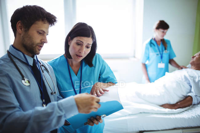 Hombre doctor y enfermera interactuando sobre un informe en el hospital - foto de stock