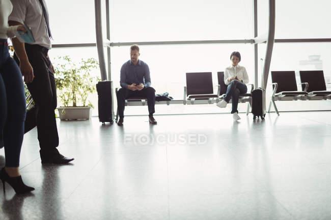 Les gens d'affaires utilisant le téléphone mobile dans la salle d'attente à l'aérogare — Photo de stock