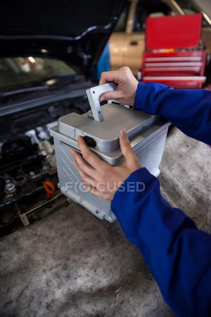 Imagen recortada de mecánico quitar la batería del coche en el garaje de reparación - foto de stock
