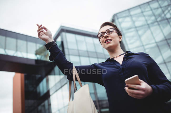 Low angle view of businesswoman gesturing outside office building — Stock Photo