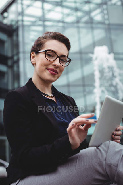 Portrait of smiling businesswoman using digital tablet outside office — Stock Photo