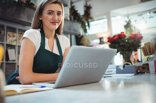 Female florist standing with laptop in the flower shop — Stock Photo