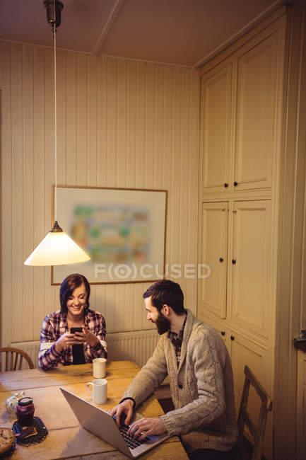 Пара с помощью ноутбука и мобильного телефона дома — стоковое фото