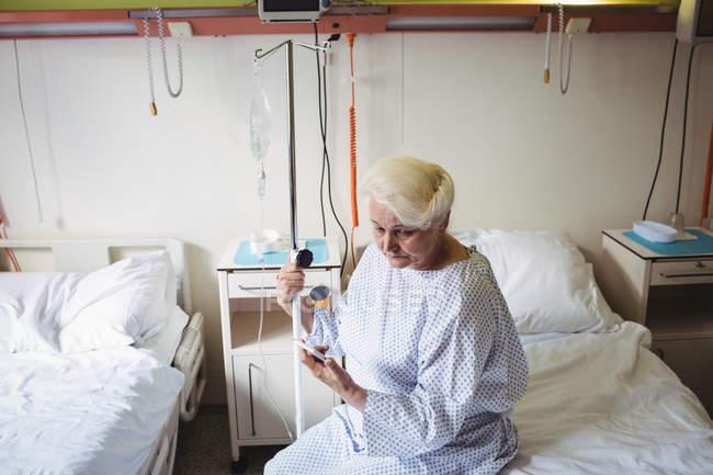 Mujer mayor mirando el teléfono móvil en el hospital - foto de stock