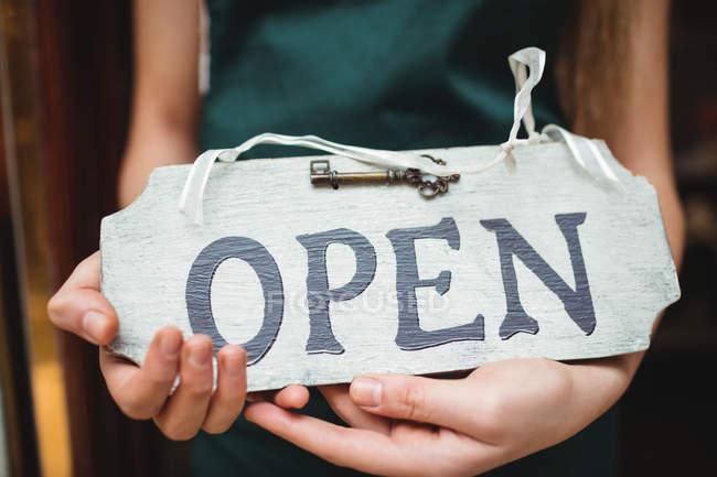 Immagine potata della donna che tiene aperto insegna presso il suo negozio — Foto stock