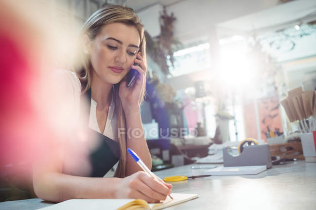 Floristería mujer teniendo orden de móvil en la tienda de la flor - foto de stock
