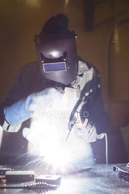 Female welder working on piece of metal in workshop — Stock Photo