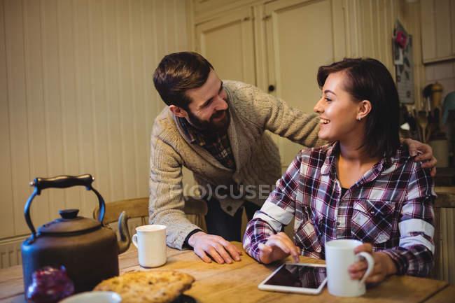 Пара взаимодействует друг с другом за чашечкой кофе дома — стоковое фото