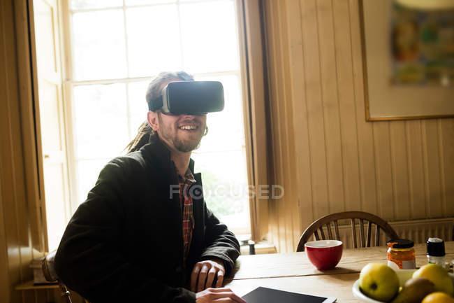Smiling young man using virtual reality simulator at home — Stock Photo